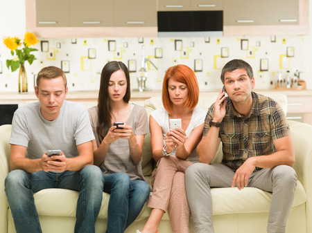 friends sitting on sofa and playing on their phones photo