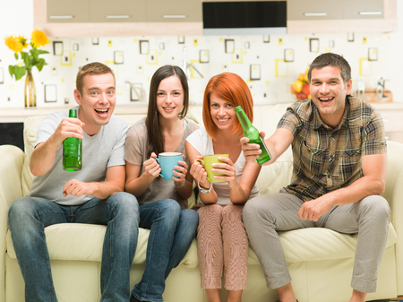 television show: portrait of four young caucasian friends sitting on sofa holding drinks, watching a television show