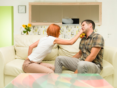 young upset caucasian woman sitting on sofa, punching man sitting next to her photo