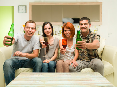 friends sitting at home on sofa, making a toast with drinks and watching tv photo