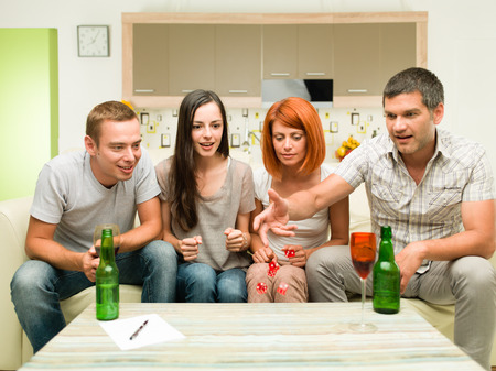 dice: friends sitting on sofa, playing game with dices and having fun Stock Photo