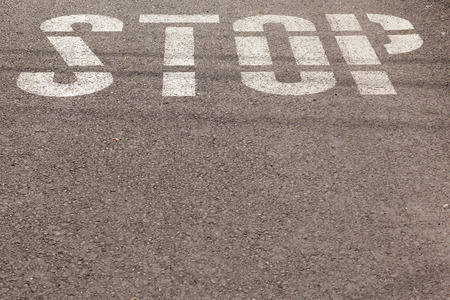 metal sign: stop sign painted on asphalt Stock Photo