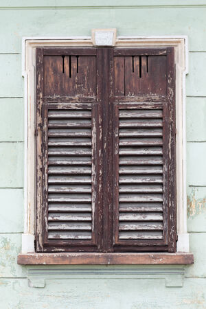 rustic old window closed with wooden exterior shutters photo