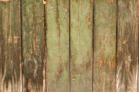 green door: old wooden fence with paint flaking orange green Stock Photo