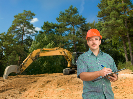 caucasian male architect taking notes on clipboard at construction site photo