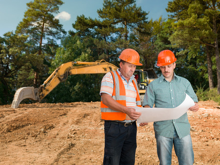 two caucasian engineers on construction site looking at plan and discussing it photo