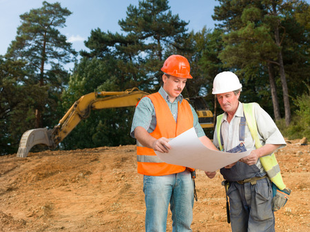 front view of manager and builder on construction site looking at blueprint and discussing it photo