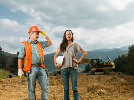 male and female engineers standing on construction site outdoors photo