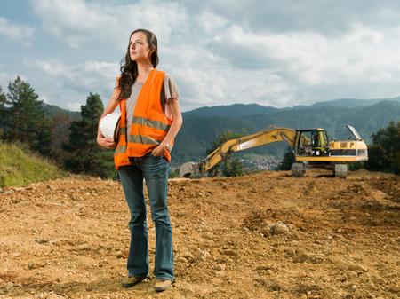 女性エンジニア バック グラウンドで掘削機が屋外で建設現場で労働者
