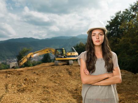 maquinaria pesada: retrato de la joven mujer ingeniero caucásico en el sitio de la construcción con excavadora en el fondo Foto de archivo