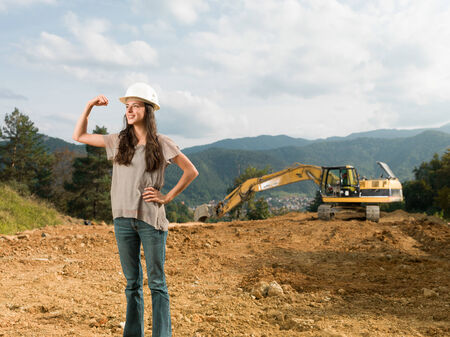 tricep: young happy caucasian female engineer showing her strenght and muscles on construction site
