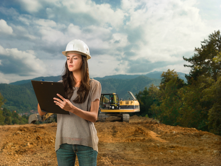 portrait of young caucasian female architect standing on construction site, holding clipboard and writing photo