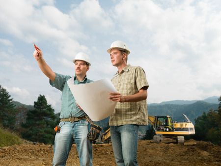 two handsome caucasian engineers comparing blueprint with actual construction photo