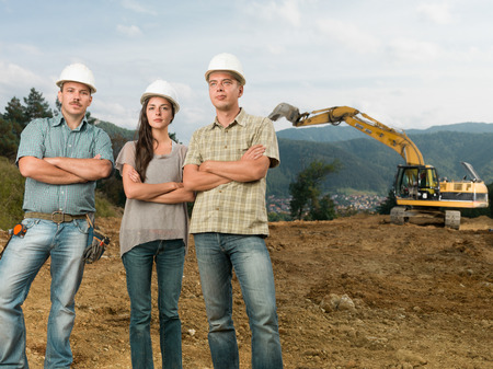 group of three caucasian architects standing with arms crossed on construction site outdoors photo
