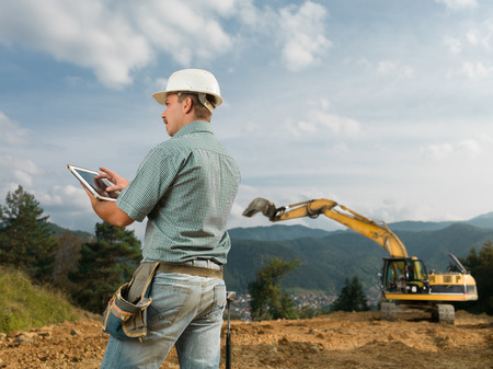 executive helmet: back view of caucasian engineer standing on construction site browsing on digital tablet