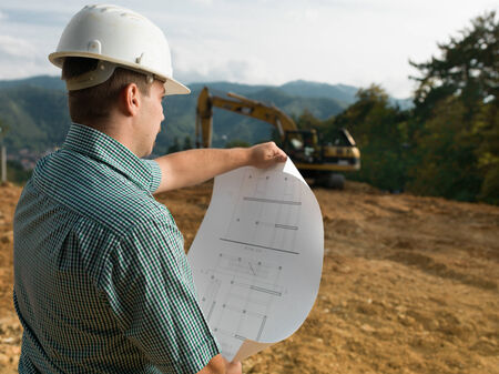 safety check: back view of male engineer standing on construction site reading blueprint