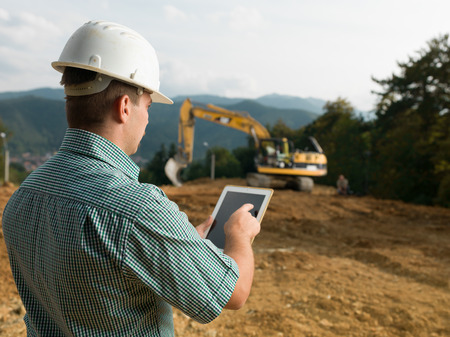 back view of caucasian engineer standing on construction site checking plan on digital tablet Archivio Fotografico