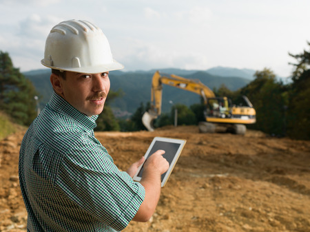 portrait of young caucasian engineer on construction site holding digital tablet