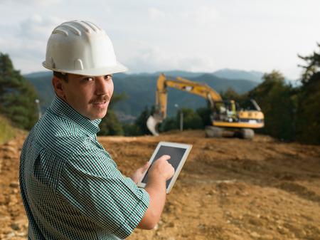 portret van Kaukasische jonge ingenieur op bouwwerf die digitale tablet