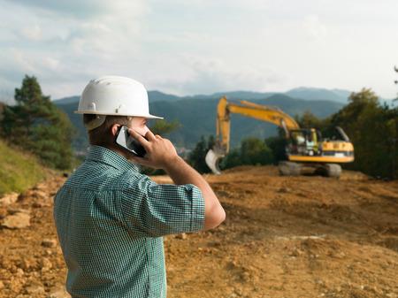 edificio industrial: Ingeniero de sexo masculino de hablar por tel�fono mientras supervisaba la construcci�n
