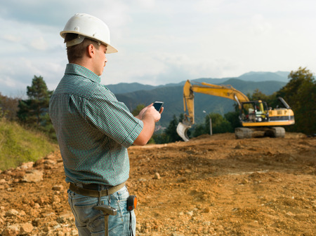 construction work: side view of male engineer standing on construction site holding mobile phone Stock Photo