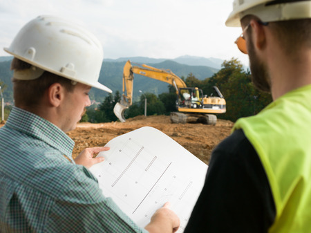 back view of two contractors looking at construction plan on worksite