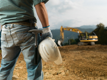 closeup back view of male engineer standing on construction site holding white hardhat photo