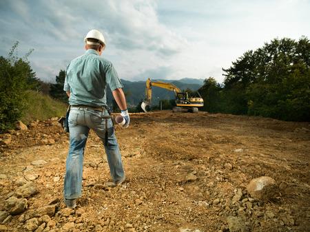 achteraanzicht van ingenieur houden blauwdruk, het lopen op de bouwplaats naar graafmachine