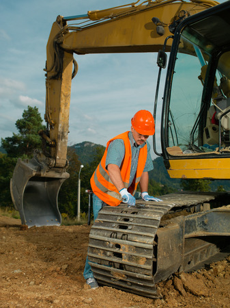 digger: male construction worker repairing excavator track Stock Photo