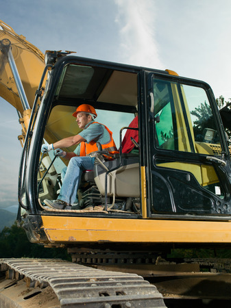 male worker operating excavator on construction site