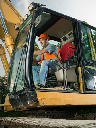 heavy equipment operator: happy male worker operating excavator on construction site Stock Photo