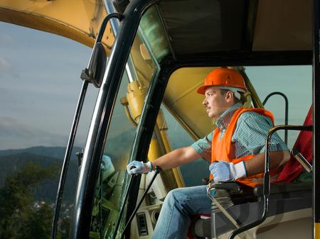 maquinaria pesada: masculino excavadora de conducción del operador en el sitio de construcción de la construcción