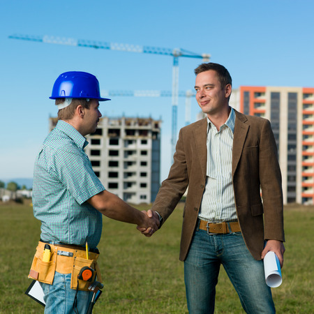 architect and construction engineer standing and shaking hands on construction site outdoors photo