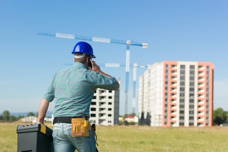 hand job: back view of caucasian enginner talking on phone at residential construction site