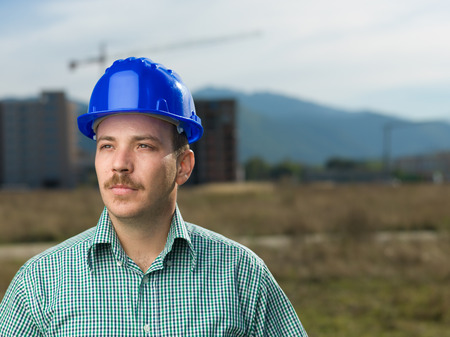 portrait of handsome caucasian engineer on construction site outdoors photo