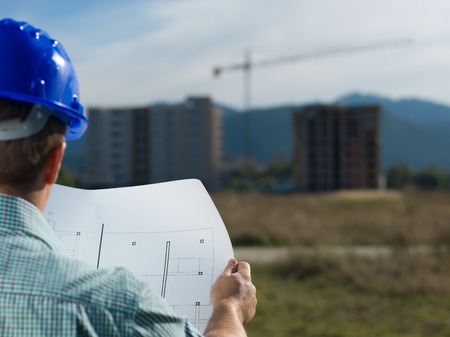 site manager: back view, closeup of male caucasian engineer at work looking at technical drawing plan