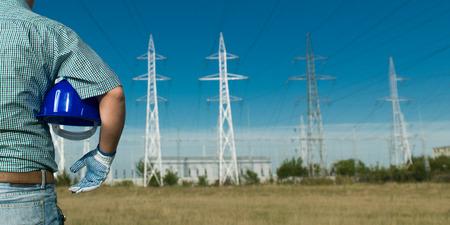ingeniero electrico: vista atrás, de cerca de ingeniero masculina de pie en la estación de energía eléctrica, casco celebración