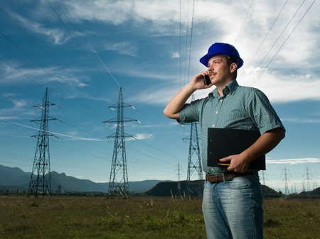 outdoor electricity: portrait of male technician writing on clipboard at electricity station