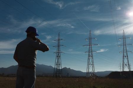 cables electricos: silueta de ingeniero de pie en el campo con torres de electricidad, hablando por el teléfono Foto de archivo