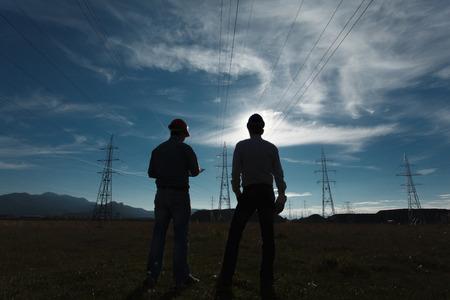Silueta de dos ingenieros de pie en la estación de energía eléctrica en el ocaso Foto de archivo - 33008340