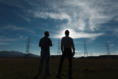 redes electricas: silueta de dos ingenieros de pie en la estación de energía eléctrica en el ocaso