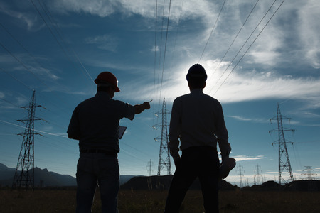 ingeniero: silueta de dos ingenieros de pie en la estación de energía eléctrica en el ocaso