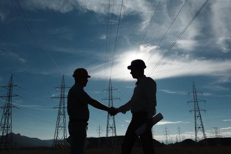 일몰에 전기 역에 서있는 두 엔지니어의 실루엣