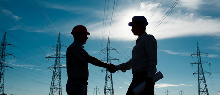 silhouette of two engineers standing at electricity station at sundown photo