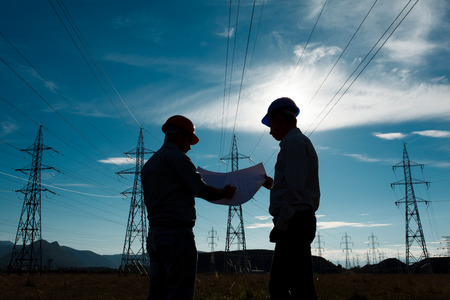 workers: silueta de dos ingenieros de pie en la estaci�n de energ�a el�ctrica en el ocaso