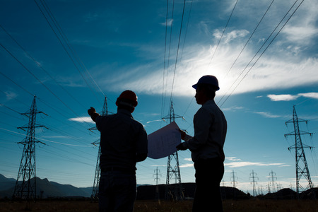 high voltage: silhouette of two engineers standing at electricity station at sundown