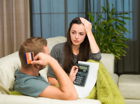 caucasian couple sitting on couch at home calculating expenses