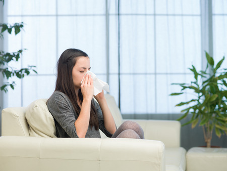 eyesclosed: young caucasian woman sitting on couch at home, blowing nose with tissue Stock Photo
