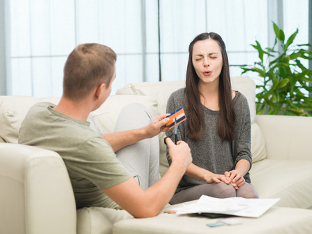 whining: man cuts credit card in front of his upset girlfriend Stock Photo