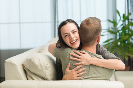 portrait of young caucasian couple relaxing on sofa at home, embracing each other and having fun photo